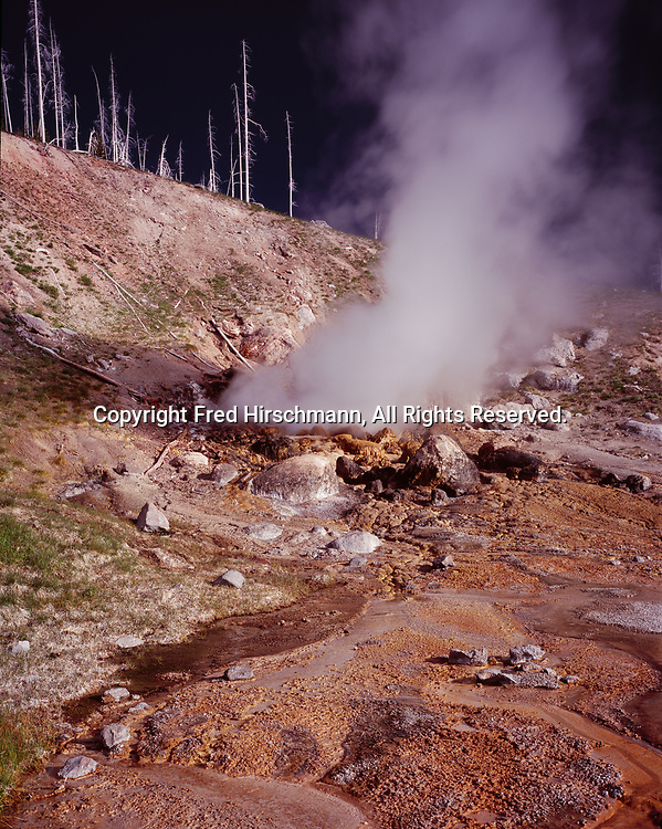 Eruption of Oblique Geyser with storm clouds beyond, Geyser Springs Group, Geyser Creek, Gibbon Geyser Basin, Yellowstone National Park, Wyoming.
