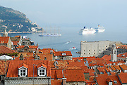 Elevated view of Dubrovnik old town, with harbour, cruise ships and replica sailing ship in background. Dubrovnik, Croatia