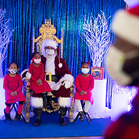 PHILADELPHIA, PA:  (L-R) Genesis, Nahlah, and Winter Kersey, all 4, pose with Santa in Philadelphia, PA on December 12, 2020.  The pandemic has forced difficult decisions about maintaining the holiday tradition of visits to Santa Claus versus safety concerns.  Plexiglass dividers, face shields, and physical distancing are among the precautions for those locations that have proceeded with Santa photo opportunities.  CREDIT:  Mark Makela for The New York Times