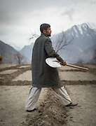 A farmer making small mud wall separations before flooding his potatoe field.  In the village of Duikar, above Karimabad village, Hunza region.
