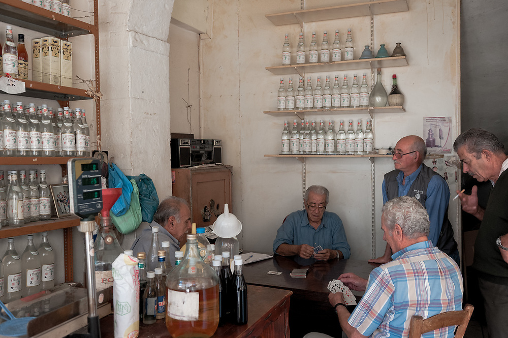 Old men playing cards at the shop of the traditional Tsamparlis Distillery in Chios town. The distillery was founded in 1914 and it still run by the same family. It produces Ouzo, Mastic Liqueur and Tangerine Liqueur