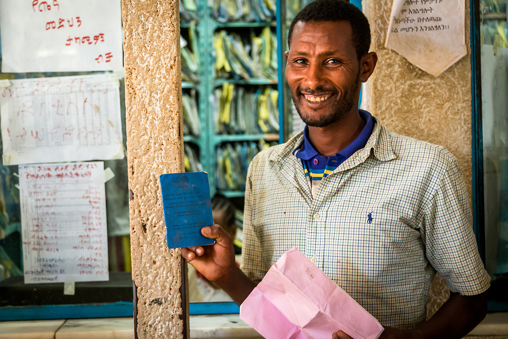 INDIVIDUAL(S) PHOTOGRAPHED: Mola Simegn. LOCATION: Felege Hiwot Referral Hospital, Bahir Dar, Ethiopia. CAPTION: Mola Simegn, a Community-Based Health Insurance (CBHI) beneficiary, proudly smiles while showing his membership card. The HFG Project has worked to support the Ethiopian government in implementing CBHI. CBHI insurance is designed to benefit Ethiopian citizens who are engaged in the informal sector.