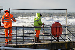 © London News Pictures. 08/12/2017. Aberystwyth, UK.<br /> Local authority workers erect safety barriers to prevent the public from accessing the seaside jetty and more huge waves crash against the shore. The southern edge of Storm Caroline, with winds gusting between 40 and 60 mph, is still impacting on the harbour lighthouse  sea defences  in Aberystwyth, Ceredigion , west Wales UK. Photo credit: Keith Morris/LNP