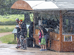 Licensed to London News Pictures. 06/08/202. London, UK. With weather more like September, walkers and cyclists shelter from the rain in Richmond Park, southwest London as wind and rain is set to hit the South East today. Yellow weather warnings for England have been issued for heavy rain, flooding, and high winds as the bad weather is expected to continue throughout the weekend. However brighter weather is forecast for next week with highs of 22c. Photo credit: Alex Lentati/LNP