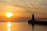 The ice laden South Pier Lighthouse stands watch as a sunset lights up the wintry sky in South Haven