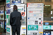 man buying cigarettes at an outdoor vending machine Kyoto Japan