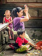 11 OCTOBER 2016 - UBUD, BALI, INDONESIA: A woman and her sons pray at the Hindu temple in the market in Ubud. The temple in the market is very busy during the midmorning hours, when market vendors come to pray. The morning market in Ubud is for produce and meat and serves local people from about 4:30 AM until about 7:30 AM. As the morning progresses the local vendors pack up and leave and vendors selling tourist curios move in. By about 8:30 AM the market is mostly a tourist market selling curios to tourists. Ubud is Bali's art and cultural center.      PHOTO BY JACK KURTZ