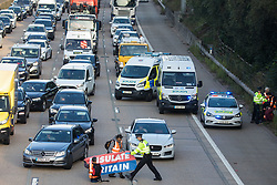 Ockham, UK. 21st September, 2021. A Surrey Police officer intervenes to remove a banner from Insulate Britain climate activists blocking the anticlockwise carriageway of the M25 between Junctions 9 and 10 where they had been protesting as part of a campaign intended to push the UK government to make significant legislative change to start lowering emissions. Both carriageways were briefly blocked before being cleared by Surrey Police. The activists are demanding that the government immediately promises both to fully fund and ensure the insulation of all social housing in Britain by 2025 and to produce within four months a legally binding national plan to fully fund and ensure the full low-energy and low-carbon whole-house retrofit, with no externalised costs, of all homes in Britain by 2030.