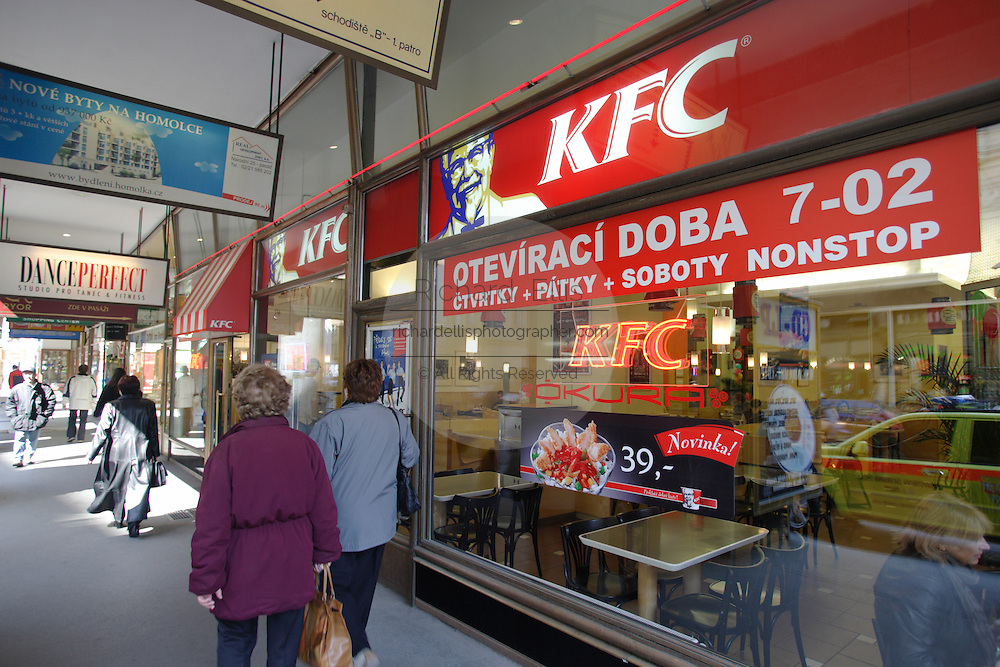People walk past a Kentucky Fried Chick fastfood franchise with signs in Czech along a street in the old section of the city.