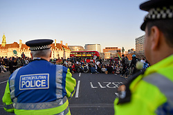 © Licensed to London News Pictures 15/02/2019 London, UK. Police look on as a routemaster bus is forced to make a u-turn on Westminster Bridge as schoolchildren stage a sit-down. At the close of a day of protest, students who took the day off school to protest inaction over climate change move from Parliament Square to Westminster Bridge blocking traffic at rush hour. Photo credit: Guilhem Baker/LNP