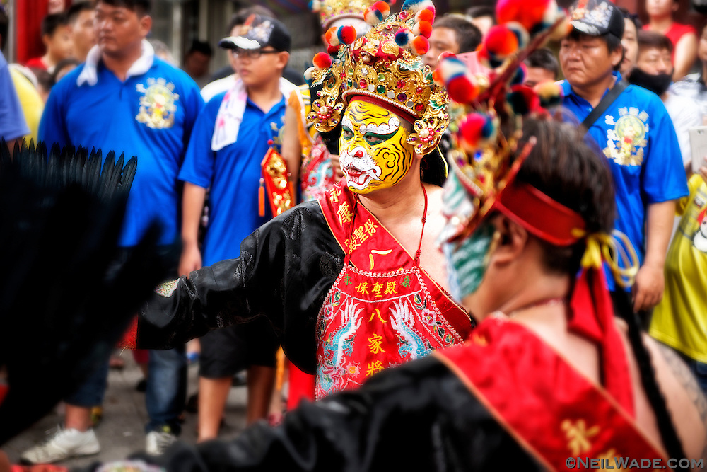 A dancer with a painted tiger face, said to be possessed by the spirit of a Taoist God, dances at a religious ceremony in Tainan, Taiwan.