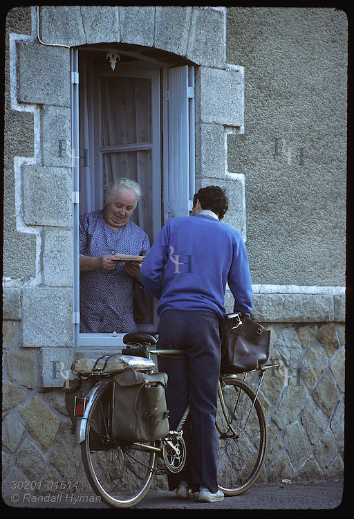 Woman at window of her house in Locmariaquer receives letters from town's bike-riding mailman. France