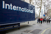 International tourists walk past an articulated lorry with the word International emblazoned on the side on 7th March 2020 in London, United Kingdom. London as a tourist destination is full of groups of young students.