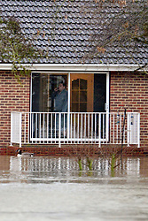 © Licensed to London News Pictures. 11/02/2014. Laleham, UK . A man looks out of his window. Flooding in LALEHAM in Surrey today 11th February 2014 after the River Thames burst its banks. The Environment Agency has issued 14 Severe Flood Warnings alone the Thames. Photo credit : Stephen Simpson/LNP