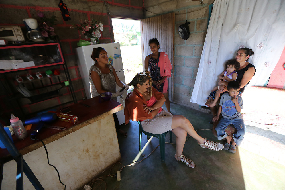 Marcia Verónica Elvir Romero, 28, madre de cuatro hijos, y esperando el número cinco.<br /> <br /> La idea era esa, llegar a los Estados Unidos. <br /> <br /> Pero cuando íbamos por Mexico, y los Zetas estaban empezando a secuestrar las personas, mejor decidimos venir. Ya estábamos en México, trabajamos allí, para hacer el pasaje, y nos venimos.<br /> <br /> Nos venimos el 22 de diciembre del año pasado, un año ya. Estuvimos allí más de un mes. <br /> <br /> Cuando llegamos, alguien nos dijo del programa.<br /> <br /> Yo ya tenía me salón de belleza. Le digo salón verdad, porque esta en mi salón de estar, aquí en mi casa. <br /> <br /> Me han ayudado con capacitación, y con muebles, sillas, espejos, la mesa para manicure, la silla de manicure. <br /> <br /> He ido a varias capacitaciones, hasta en Tegucigalpa. La semana pasada vino una técnica que contrataron para dar cursos de bellezas, me ha venido a visitar.<br /> <br /> Ya voy a perder algunas reuniones porque ya me toca [dar la luz]. Me dieron reposo, y míreme, trabajando. <br /> <br /> Me dijo la doctora que ya no hay problema que nazca el bebé.<br /> <br /> En México yo no salía, me daba miedo que nos viera la migración o las bandas criminales como son los zetas, no quería que nos secuestraran, o que nos sacaran. La familia de mi esposo tiene un amigo allí que nos dieron donde quedar. Y yo trabajé en un salón de belleza, cortando pelo. Pero no salía, tenía mucho miedo. La verdad es que tuvimos mucha suerte que no nos pasó nada fuerte, como suele pasar.<br /> <br /> Ahora, con el bebé que viene, y con estas capacitaciones y el apoyo de la Federación, siento esperanza, que todo va a salir bien aquí. No deja de ser una lucha, pero ya tenemos algo para ir trabajando.