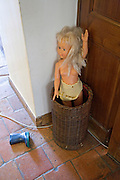 a doll placed inside by the door in an umbrella basket