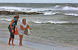 October 7, 2016 - Treasure Island, Florida, U.S. - SCOTT KEELER   |   Times. Left to Right: Visitors Staci Devick, Reinbeck, Iowa and Debbie Barber, La Porte City, Iowa, look for shells on Sunset Beach, Treasure Island in a stiff northwest wind from Hurricane Matthew, Friday, 10/7/16. Both said the shelling was good from the large waves. (Credit Image: © Scott Keeler/Tampa Bay Times via ZUMA Wire)