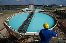 Inspector Guido De Rycke looks over brine tanks at the Solvay SA chemical plant in Antwerp, Belgium, on Thursday, April 22, 2010. The blue color is caused by the high concentration of salt, which is used to make chlorine, the main product of the Solvay's Antwerp facility.  Solvay SA is the world's largest supplier of Soda Ash or Sodium Carbonate and is also a major producer of caustic soda, hydrogen peroxide, chlorine and fluorinated products. (Photo © Jock Fistick)
