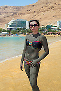 Young Caucasian tourist covered in therapeutical mud at a Dead Sea resort, Israel Model released