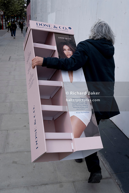 Days before the third Coronavirus lockdown ends, and non-essential retailers and shops re-open again, a man carries retail merchandising that features the face of Kloe Kardashian along Oxford Street, on 9th April 2021, in London, England.