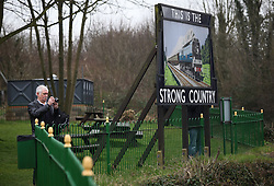 © Licensed to London News Pictures. 07/03/2014. Hampshire, UK. A train spotter standing next to a sign that reads 'THIS IS THE STRONG COUNTRY' at Alresford Station today, 7th March 2014, which is the first day of the 'spring steam gala' on the Watercress Line. The railway line, operated by Mid Hants Railway Ltd, passes between Alresford and Alton in Hampshire. The line is named after its use in the past for transporting freshly cut watercress from the beds surrounding Alresford to London. Photo credit : Rob Arnold/LNP