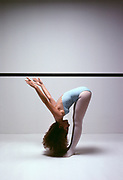 Woman ballet dancer bent over and stretching at the exercise dance bar