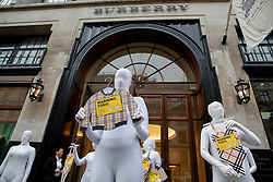© Licensed to London News Pictures. 24/01/2014. London, United Kingdom. Greenpeace activists hold a demonstration outside the flagship Burberry store on Regent's Street, London. The protest, called Detox, aimed to highlight the dangers of the chemicals used in Burberry clothing. Photo credit : Thomas Harrison/LNP