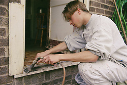 Young painter and decorator working on door frame of house,