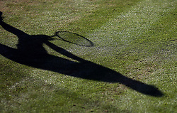 The shadow of a tennis player on court on day six of the Wimbledon Championships at the All England Lawn Tennis and Croquet Club, Wimbledon.