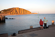 Golden afternoon light on sandstone cliffs, East Cliffs, West Bay, Bridport, Dorset, England, UK with father and son fishing in the foreground