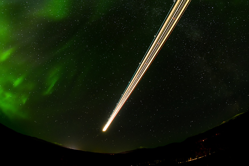 A time exposure captures the lights of an Air North 737-500 with the aurora in the background