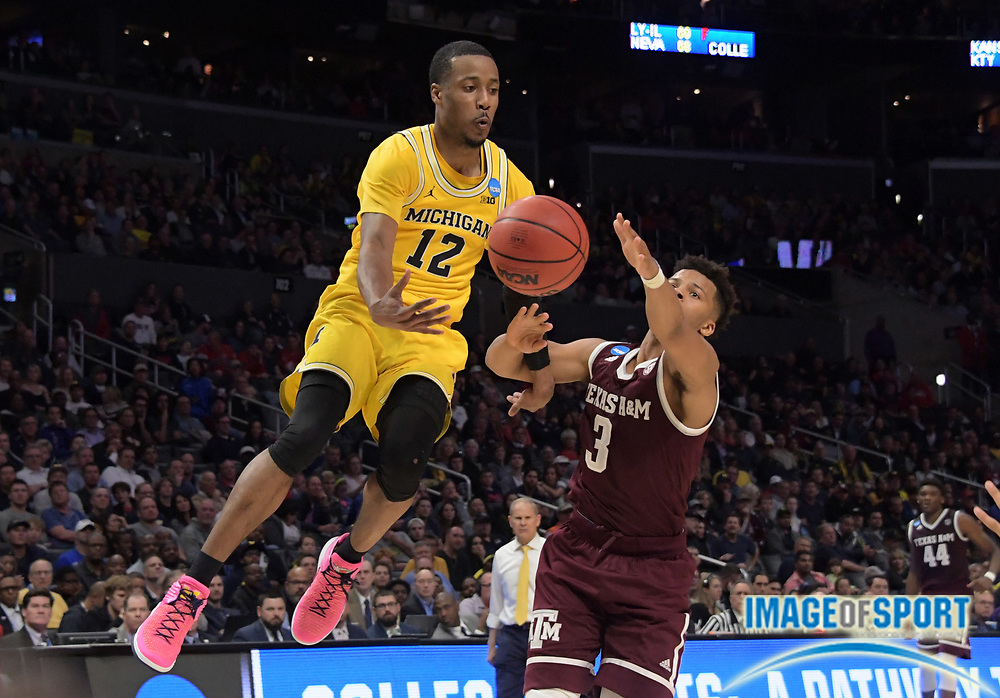Michigan Wolverines guard Muhammad-Ali Abdur-Rahkman (12) passes the ball as Texas A&M Aggies guard Admon Gilder (3) defends during a West Regional semifinal of the NCAA men's college basketball tournament, Thursday, March 22, 2018, in Los Angeles. Michigan defeated Texas A&M 99-72.