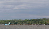 Cornwall-on-Hudson, New York - The tugboat Cheyenne pushes a barge down the Hudson River as a sailboat, at right, heads north on April 27, 2010.
