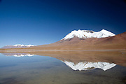 A snow capped volcano next to a loagoon. Salar Uyuni salt flats and Eduardo Avaroa national park, south western Bolivia