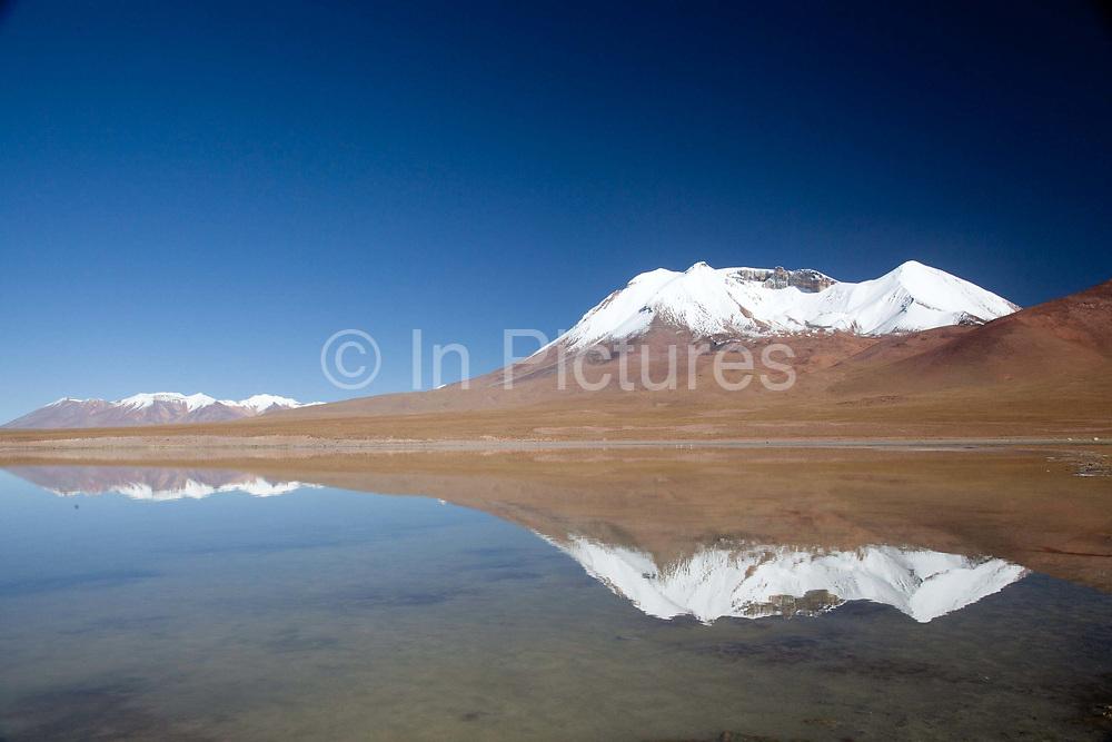 A snow capped volcano next to a loagoon. Salar Uyuni salt flats and Eduardo Avaroa national park, south western Bolivia