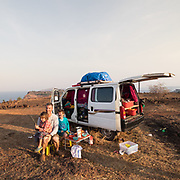 Father and his 2 sons having breakfast next to their camping car - camper van.