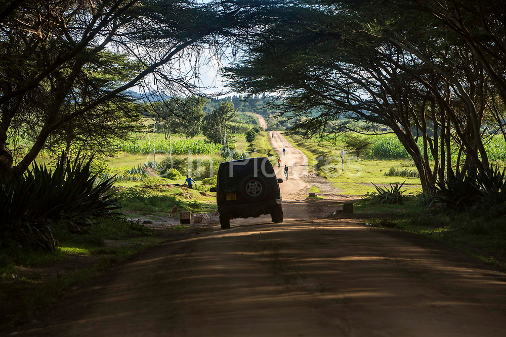 Land Rover 4x4 car drives along a dirt road track towards pedestrians and cyclists on the road to Mbulu, Manyara district, Tanzania, East Africa.