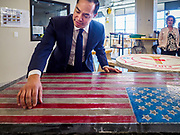 15 APRIL 2019 - DES MOINES, IOWA: JULIÁN CASTRO, on a visit to the Central Campus Skilled Trades Alliance at the Des Moines Public School's Central Campus, looks at a table with an American flag on it that was made at the Skilled Trades Alliance. Castro is on his third visit to Iowa since declaring his candidacy for the Democratic ticket of the US Presidency. Casto talked to students and administrators about skilled trades education and toured the campus. Iowa traditionally hosts the the first selection event of the presidential election cycle. The Iowa Caucuses will be on Feb. 3, 2020.                PHOTO BY JACK KURTZ