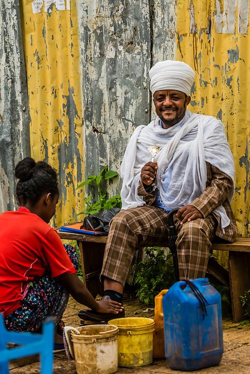 Man getting a shoe shine on the street in Bahir Dar, Ethiopia