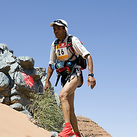 26 March 2007: #26 Amine Kabbaj of Morocco reaches summit of jebel El Otfal, 947 meters and an average 25% slope, during the second stage (21.7 miles) of the 22nd Marathon des Sables between Khermou and jebel El Otfal. The Marathon des Sables is a 6 days and 151 miles endurance race with food self sufficiency across the Sahara Desert in Morocco. Each participant must carry his, or her, own backpack containing food, sleeping gear and other material.