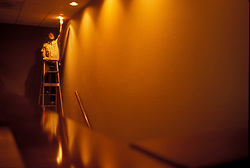 Stock photo of a man on a ladder installing new light bulbs in the recessed ceiling fixtures