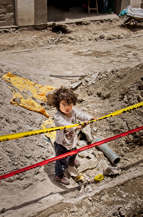 A young boy playing in a construction site, next to where a party is taking place, in Cotacachi, <br />Ecuador