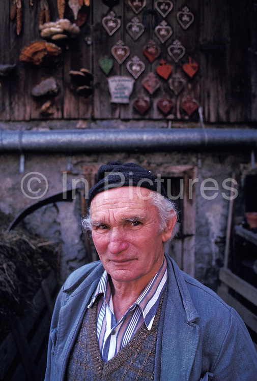 Dressed in typical overalls for the area, traditional Alpine farmer Peter Eberle works in the courtyard of his dairy and goat farm in Balzers, Liechtenstein, on 8th February 1990, in Balzers, Liechtenstein. Liechtenstein is a landlocked Principality bordered by the Alpine countries of Austria and Switzerland and is a winter sports resort, though best known as a tax haven, attracting companies worldwide to register their assets in complete secrecy. Its agricultural output is mainly wheat, barley, corn, potatoes, livestock and dairy products though technology companies have been eroding the traditional ways of life such as Peters for decades.