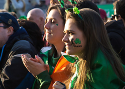 London, March 13th 2016. The annual St Patrick's Day Festival takes place in Trafalgar Square with performances on stage and plenty of Irish food and drink for the thousands of revellers.  PICTURED: Two women enjoy the late afternoon sunlight as they watch performers on stage. ©Paul Davey<br /> FOR LICENCING CONTACT: Paul Davey +44 (0) 7966 016 296 paul@pauldaveycreative.co.uk