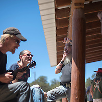 Jason Kadinger strums on his ukelele for his friends gathered outside the Candy Kitchen Trading Post during the farmer's market Wednesday in Candy Kitchen.