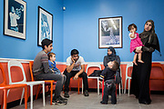 The Alsaloums pass time in the waiting room of a pediatrician's office near their temporary apartment in Tampa, Florida, U.S. They made the visit so the minors in the family could get immunizations.
