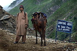"""KASHMIR,INDIA, AUGUST 3:Enveloped by the rugged and picturesque Himalayan mountains, a Bakarwal nomad leads his pony up the trail to the holy cave of Amarnath, one of the most revered of Hindu shrines, near Baltal, about 70 miles northeast of Srinagar, August 3, 2003.  The sign reads """"Shooting Area, Be Care Full"""" and is refering to falling rocks although some interpreted it as a sign warning of militant attacks. Last year, an attack was made on a base camp in Pahalgam by Islamic terrorists killing several pilgrims.  21,000 paramilitary soldiers and policemen have been deployed along the mountain route to protect the pilgrims from Islamic guerrillas, who have been fighting for independence of the Indian-controlled portion of Kashmir since 1989."""