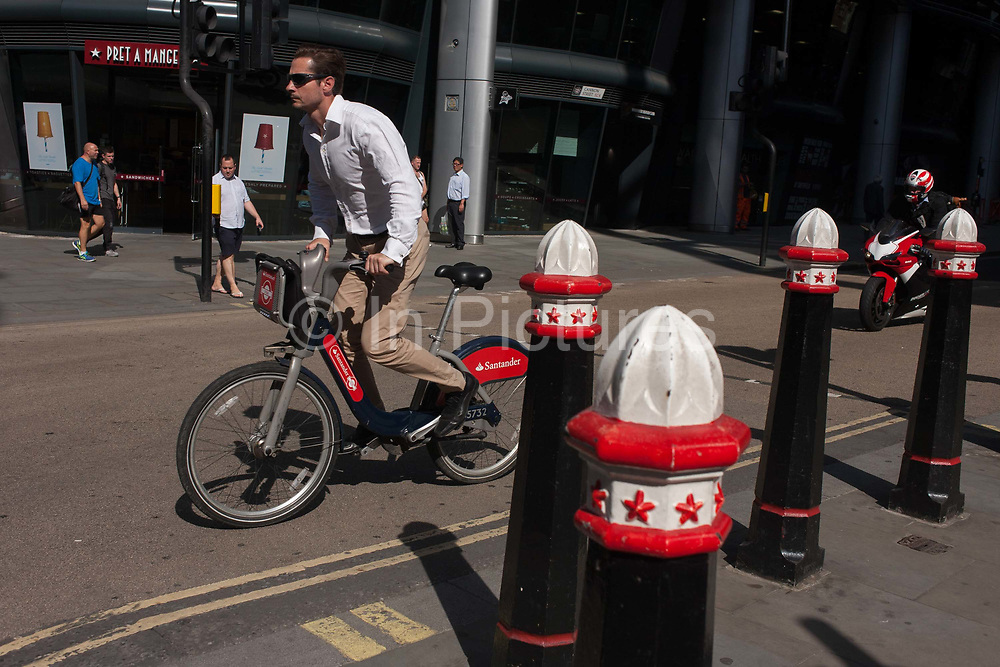 A cyclist has hired a public bike sponsored by Santander and rises off his saddle and pedals past traffic bollards on Cannon Street, on 24th August 2016, in the City of London, UK. Santander Cycles is a public bicycle hire scheme in London, United Kingdom. The schemes bicycles are popularly known as Boris Bikes, after Boris Johnson, who was the Mayor of London when the scheme was launched. This busy road runs across the capitals financial district, founded by the Romans in the first Century.