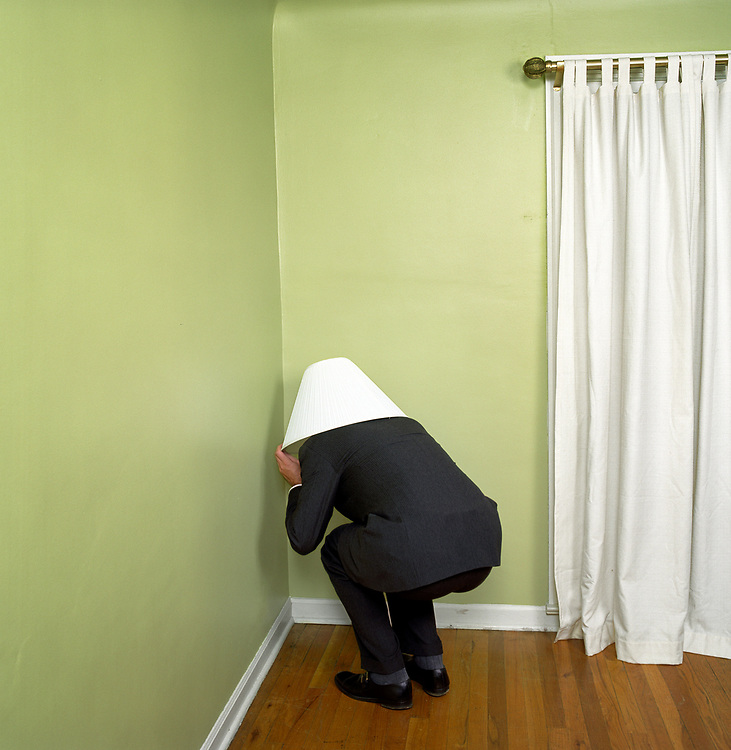 Man in business attire crouched in corner of empty living room with lampshade on head.