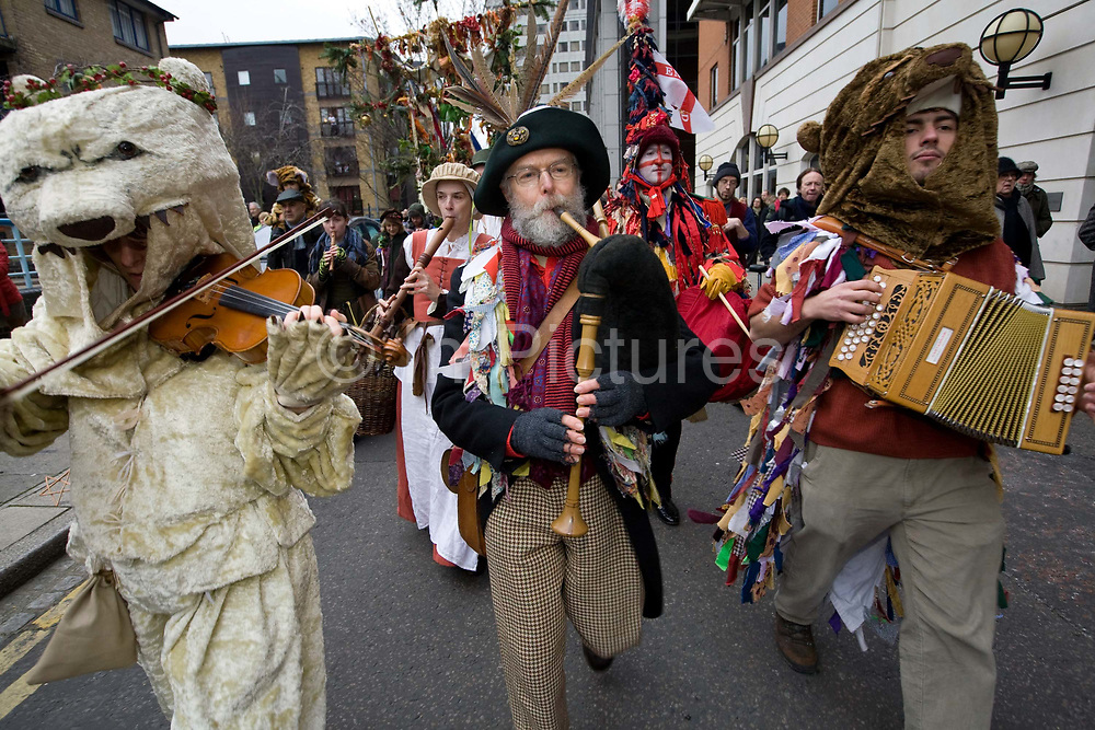 Performers and musicians from The Lions Part company play instruments to accompany an annual traditional free theatre celebrating a 'wassail' celebration to herald the new year. Bankside, London, UK. To celebrate the New Year, actors (The Bankside Mummers) associated with the Lion's Part company from the Globe Theatre, perform in traditional costume and entertain the crowds by the Thames. Participants dressed as St George and the Holly Man in the winter guise of the Green Man (a traditional pagan nature symbol) lead a procession through the streets toasting the seasons.